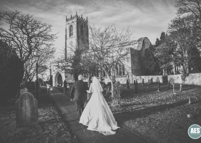 Bride and father-in-law walking towards St Mary and Martins Church in Blyth