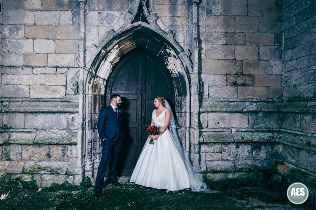 Bride and Groom inront of old door at St Mary and Martins Church in Blyth