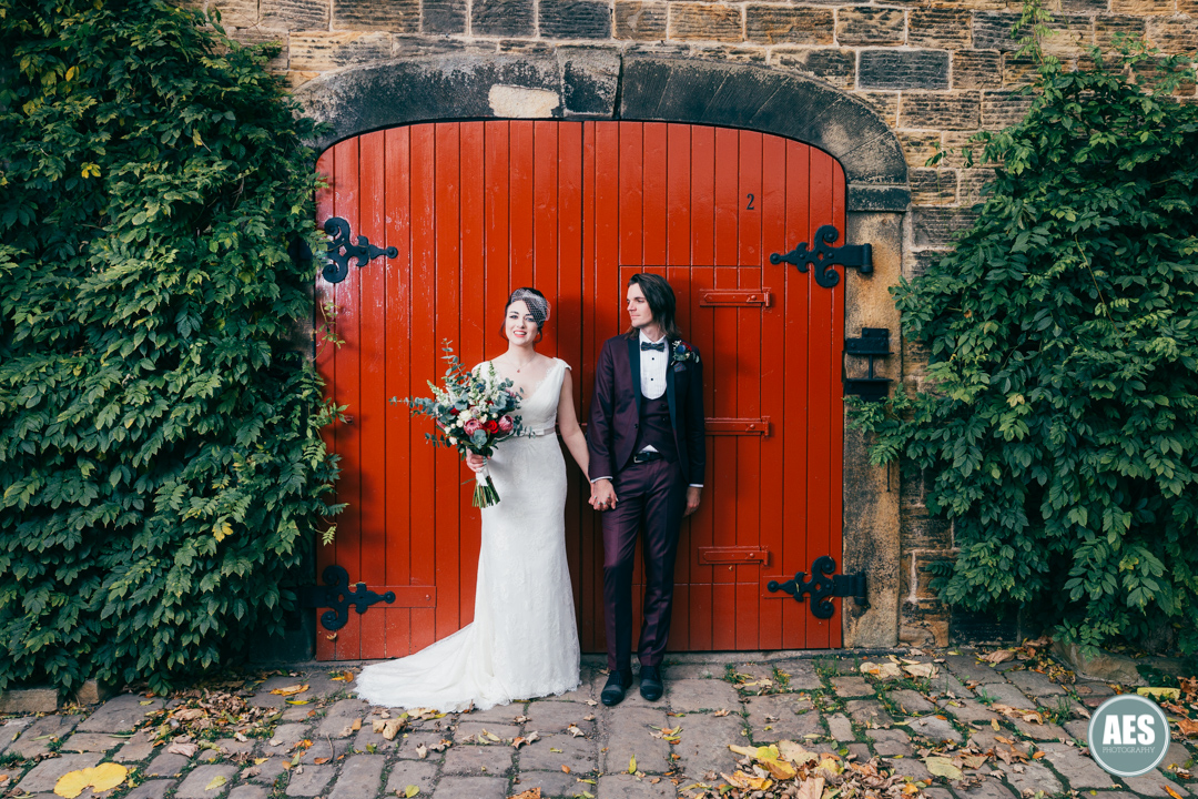 Bride and Groom in front of the red door at Wood Lane Countryside Centre